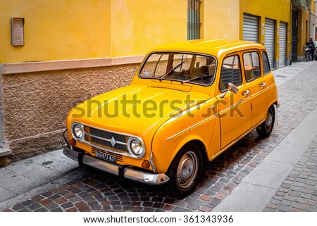 PARMA, ITALY - DECEMBER 22, 2015: Vintage orange Renault  car over stone yellow wall in Parma, Italy. - stock photo