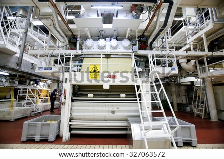 PARMA, ITALY - 3 OCTOBER 2012: Strands of spaghetti are processed ahead of packaging on the production line inside a pasta factory.