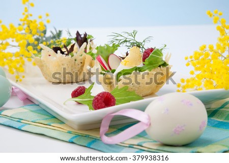 Parmesan baskets filled with fresh garden salad, hard-boiled eggs, and fresh raspberries. Easter decorated eggs, spring flowers, holiday theme. Over white.