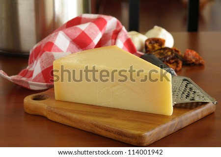 Parmesan cheese and other Italian ingredients photographed on a wooden table. - stock photo