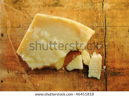 Parmesan cheese chunks on a rustic wood surface. - stock photo