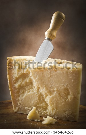 Parmesan cheese cutting on the chopping board - stock photo