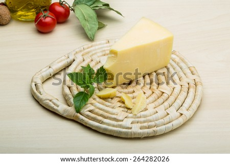 Parmesan cheese with basil leaves on the wood background