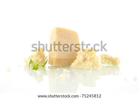 Parmesan pieces isolated on white background with basil leaves. Cheese background. - stock photo