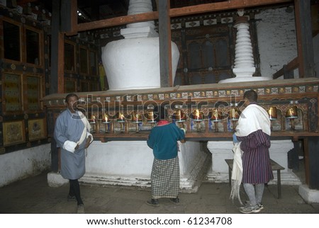 PARO, BHUTAN - APRIL 23: Bhutanese pilgrims roll the prayer wheels in Kyichu Lhakhang Monastery at April 23, 2010 in Paro, Bhutan. This monastery is one of the oldest in Bhutan.