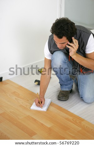 Parquet layer on phone sitting on the floor writing on a notepad - stock photo