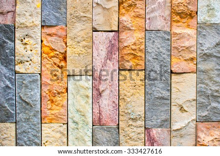 Part of a a wall of thin stone bricks, as a texture background - stock photo
