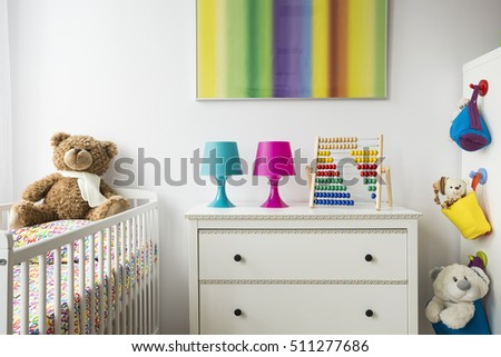 Part of a adorable child room with cradle, chest of drawers and colorful painting