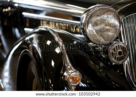 part of a black old car with headlamp - stock photo