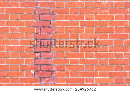 Part of a brick wall with an area of repair - stock photo