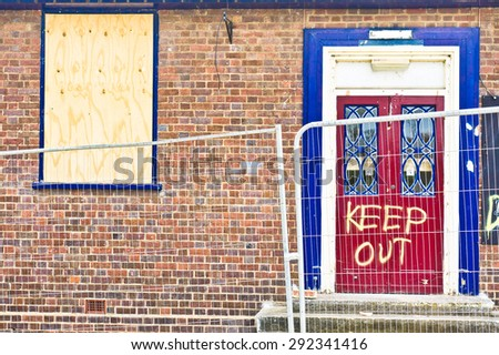Part of a building before demolition with warning graffiti - stock photo