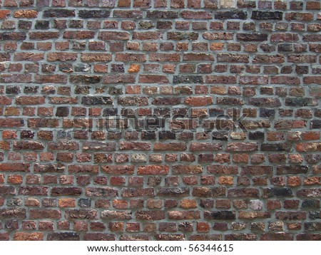 Part of a dark red brick wall