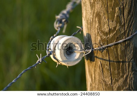 Part of a electric barbed wire fence. - stock photo