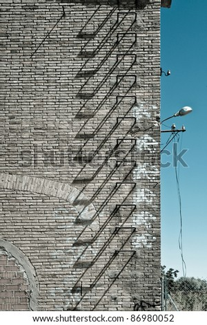 part of a facade of an abandoned factory with iron stairs for emergency - stock photo