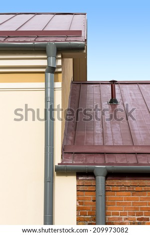 Part of a house with metal roof, wall and rain gutter