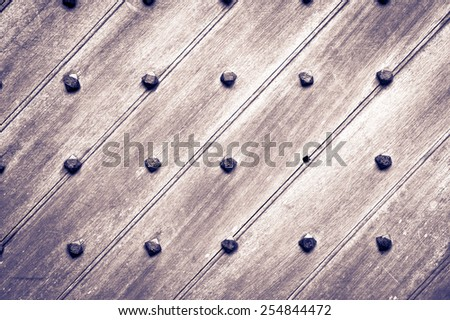 Part of a medieval door with metal studs with filter applied - stock photo
