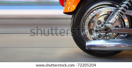 Part of a modern motorcycle with blurred road and wheels - stock photo
