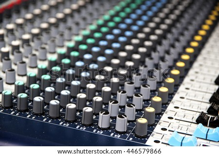 Part of a professional sound mixing console, music device for audio signals with controlling knobs and faders - stock photo