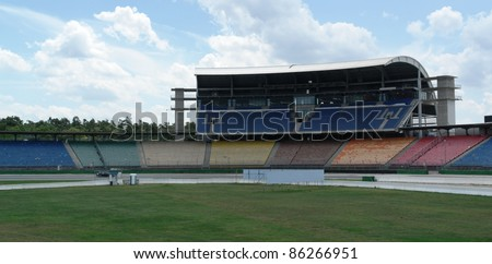 "part of a racetrack named ""Hockenheimring"" in Southern Germany with tribune and multi colored seat rows"
