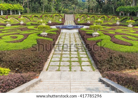 part of a regular garden with cropped hedges and fountain - stock photo