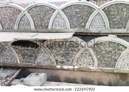 part of a stone wall, for background or texture.wall decoration with stones. pattern of modern style designer stone wall surface with cement - stock photo