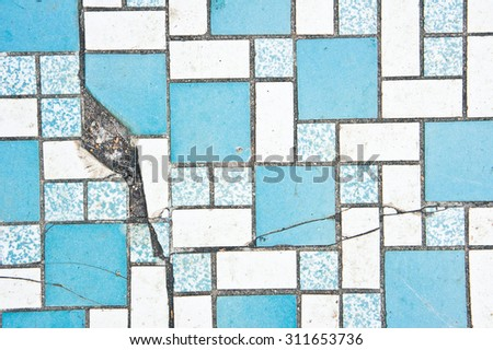 Part of a tiled surface with a crack - stock photo