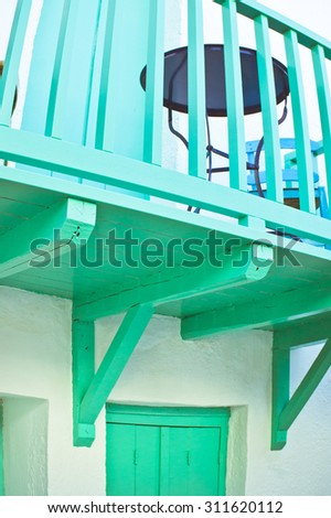 Part of a turquoise balcony on a greek house in cool tones