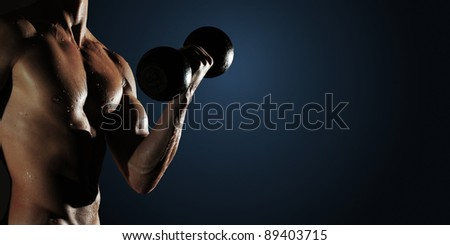 Part of a wet man's body with metal dumbbell on a dark background - stock photo