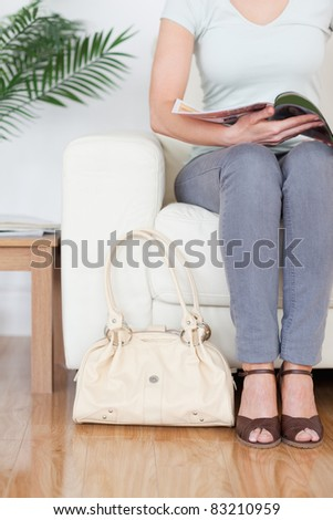 Part of a Woman on a sofa with a bag and a magazine in a waiting room - stock photo