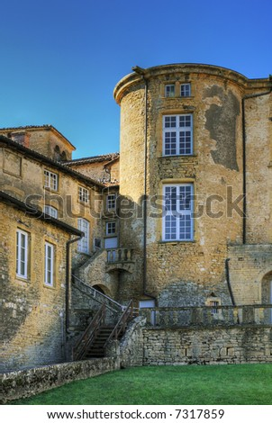 Part of a yellow castle under blue sky (Theize/France) - stock photo