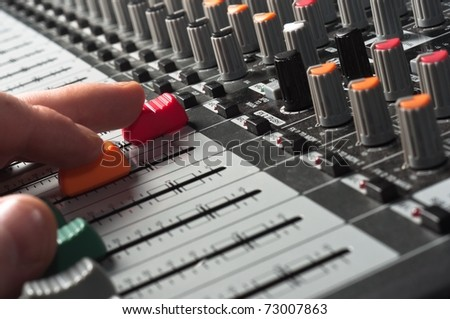 Part of an audio sound mixer with buttons and sliders and hand - stock photo
