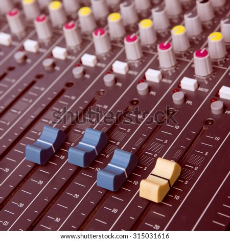 Part of an audio sound mixer with buttons and sliders - vintage filter - stock photo