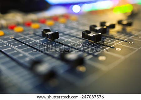 Part of an audio sound mixer with buttons and sliders. with shallow depth of field - stock photo