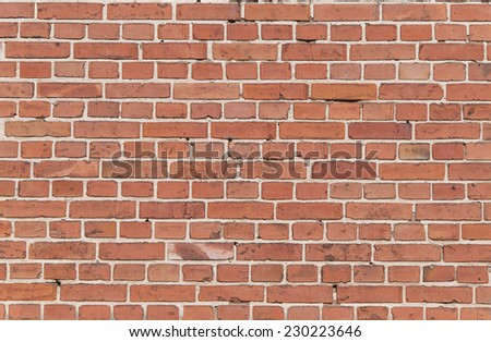 Part of an old weathered brick wall in red and brown  - stock photo