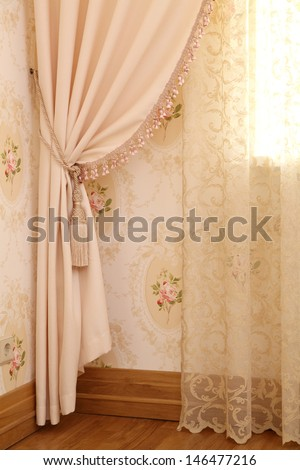 Part of beautifully draped curtain and wall with patterns - stock photo