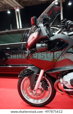 Part of black bike for cortege, car are on red carpet in exhibition
