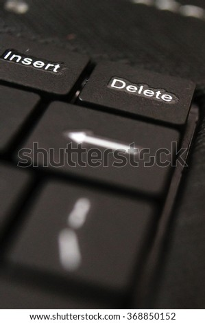 part of black keyboard laptop computer with focus on the delete button - stock photo