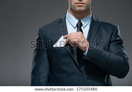 Part of body of man who pulls out white card from the pocket of business suit, copyspace - stock photo
