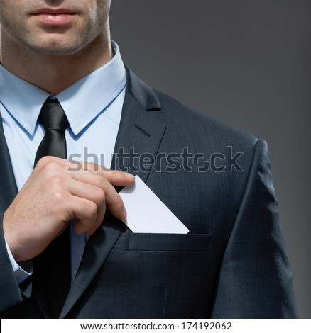 Part of body of man who takes out business card from the pocket of business suit, copyspace - stock photo