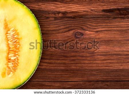 Part of cantaloupe melon halves fresh on a brown table - stock photo