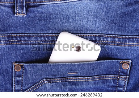 Part of cellphone in blue jeans back pocket - stock photo