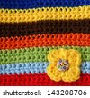 part of colorful knitted wool with knitted flower - stock photo