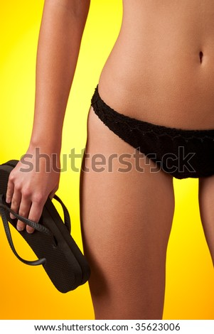 Part of female body wearing black bikini  and holding flip-flop on yellow background