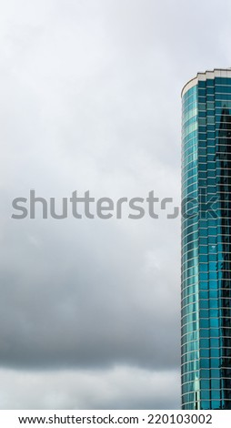 Part of Glass Curtain of An Office Building Standing Like A Cliff, Against The Dramatic Cloudy Sky  - stock photo