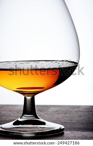Part of  glass with cognac on white background and wood base. Front view with copyspace. Close up shot. High resolution - stock photo