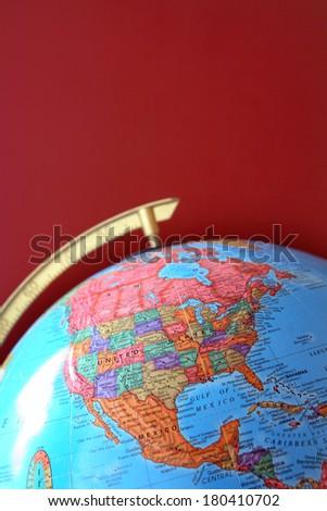 Part of globe over claret background - stock photo