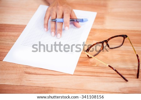 Part of hand writing notes on wooden desk
