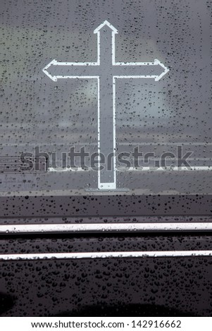 part of hearse window covered in raindrops with cross - stock photo