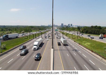 Part of Highway 401 in Toronto during the day showing the blur of traffic on the road - stock photo