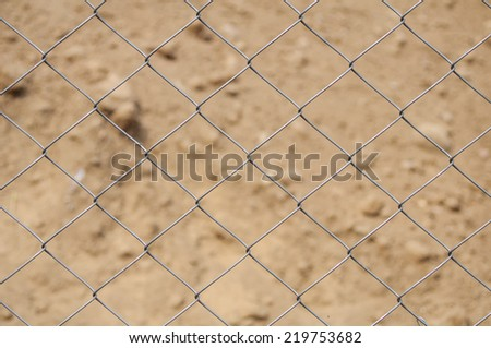 Part of mesh fence made from twisted metal wires with heap of sand at background. Closeup with shallow DOF. - stock photo